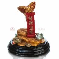 Змея с монетой на деревянной подставке